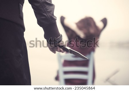 Woman killer with knife behind her victim. Edited image with vintage effect - stock photo