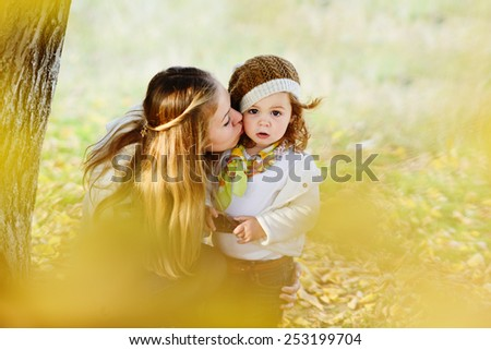 woman kissing her little daughter in fall time - stock photo