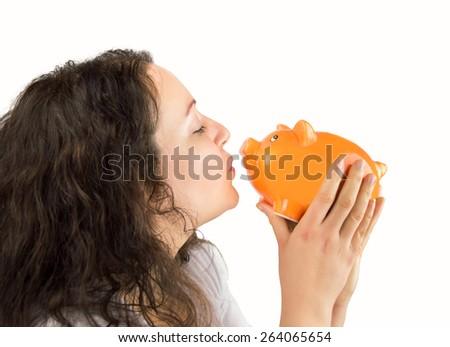 woman kissing her piggybank - stock photo