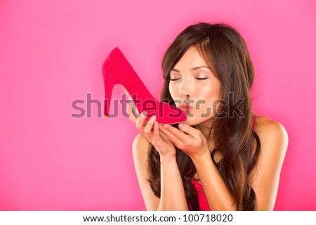 Woman kissing shoe. Women loves shoes concept. Multiracial girl and pink high heels shoes on pink background. Beautiful young happy mixed race Asian Chinese and Caucasian female model. - stock photo