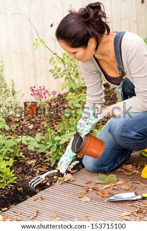Woman kneeling planting autumn garden backyard hobby rake plants housework - stock photo