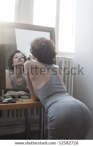 Woman kneeling while applying mascara in mirror