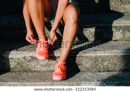 Woman lacing running and sport shoes. Sporty footwear close up. Fitness motivation and healthy lifestyle concept.