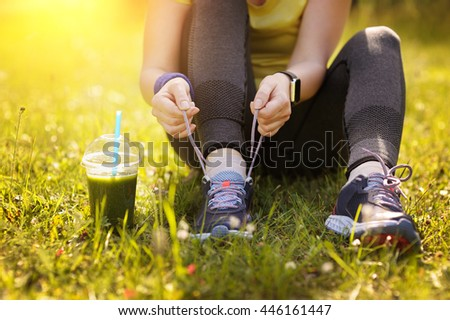 Woman lacing running shoes before workout. Fitness and healthy lifestyle concept. Green detox smoothie.