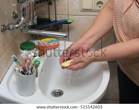 Woman lather or soap hands over sink under crane with running water.