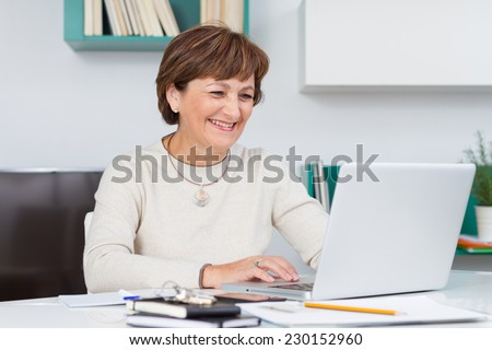 Woman laughing and smiling with computer - stock photo