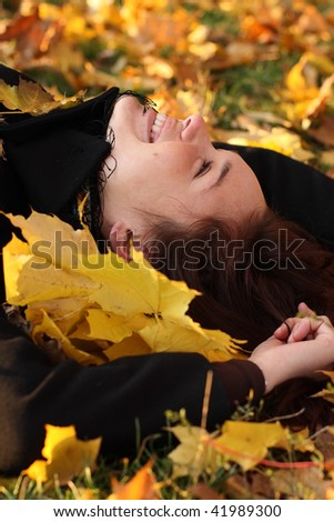 Woman laying in autumn leafs