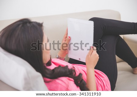 Woman laying on a couch using a tablet pc, taken from behind - stock photo