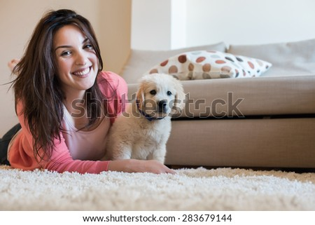 Woman laying on floor with a puppy