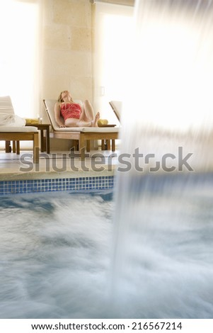 Woman laying on lounge chair near spa swimming pool with waterfall - stock photo