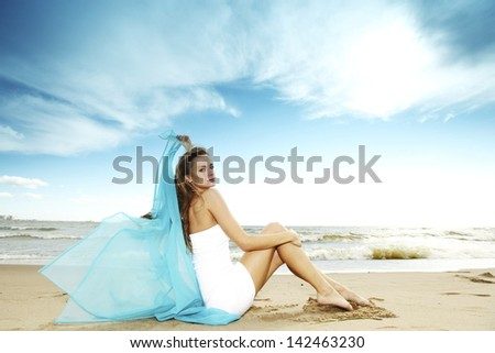 woman laying on sand sea on background - stock photo