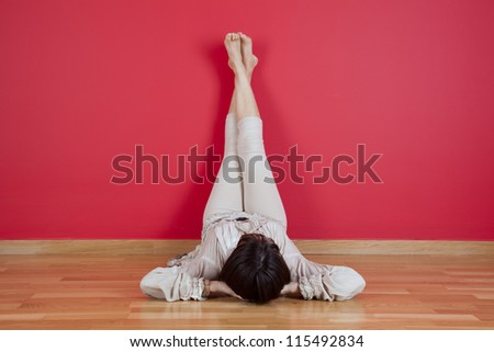 woman laying on the floor of her house next to a red wall - stock photo