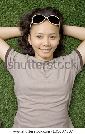 Woman laying on the green grass on the summer