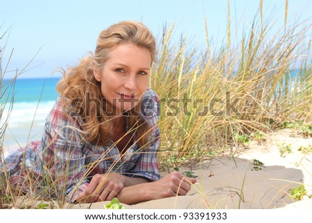 Woman laying on the sand - stock photo