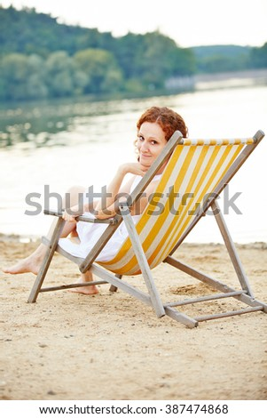Woman laying relaxed on deck chair in summer on a beach - stock photo