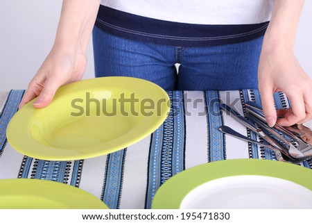 Woman laying table in room