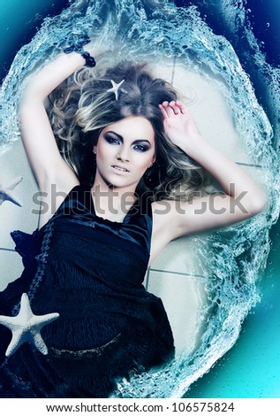 woman lays on the floor with water and sea stars