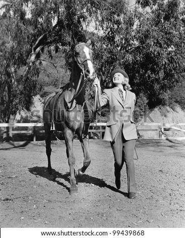 Woman leading horse - stock photo