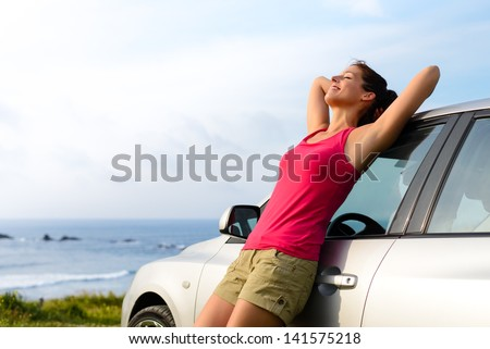 Woman leaning on car on summer travel to coast. Happy girl on road trip enjoying peace and silence relaxing on nature.