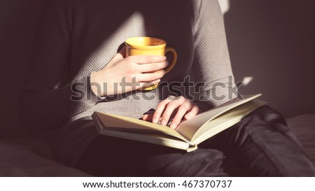 Woman learn to exam. Close-up of female hands hold open book and drink tea. Panoramic view. Panorama