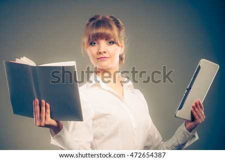Woman learning with ebook reader and book. Choice between modern educational technology and traditional way method. Girl holding digital tablet and textbook. Contemporary education. Instagram filter.