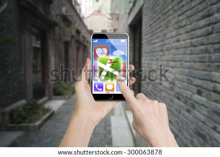 Woman left hand holding smart phone, right finger touching map icon, with daytime street background. - stock photo