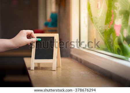 Woman left hand writing on small A-frame black board with blank area for text or message on wood bar in cafe