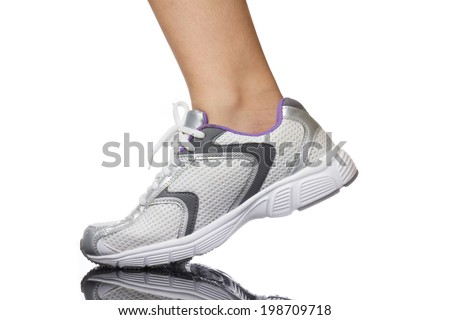Woman leg and running shoes isolated on a white background. - stock photo