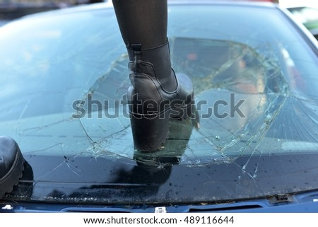 woman leg shattering the glass of a car