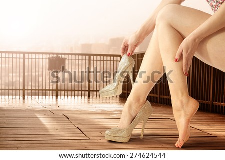 woman legs and golden heels  - stock photo