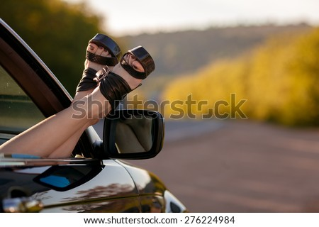 Woman legs from a car window - stock photo
