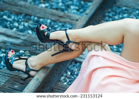 Woman legs in black high heels lying on the ground. - stock photo