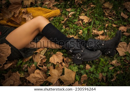 woman legs in black leather boots and leggings on grass and autumn leaves