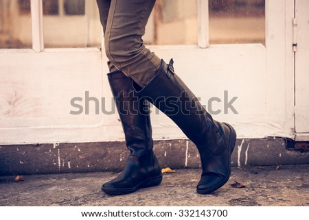woman legs in black leather high boots, pants, sweater and shirt, stand in front glass door, closeup, outdoor shot - stock photo