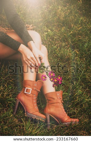 woman legs in brown ankle high heel boots sit on grass hold flowers in hands - stock photo
