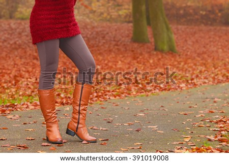 Woman legs in brown boots. Female in autumn park forest. Fall winter fashion.
