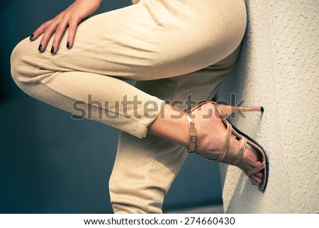 woman legs in high heel golden sandals and pants lean on wall, outdoor shot, close up - stock photo