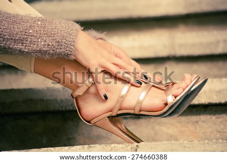 woman legs in high heel golden sandals lean on stairs, outdoor shot, close up - stock photo