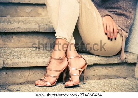 woman legs in high heel golden sandals sit on stairs, outdoor shot - stock photo