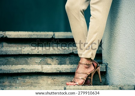woman legs in high heel golden sandals stand on stairs, outdoor shot - stock photo