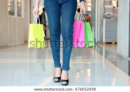 woman legs in high heel shoes Stand holding with shopping bags colorful