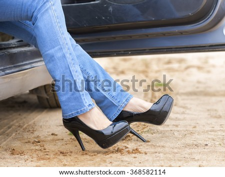 woman legs in high heels at the car