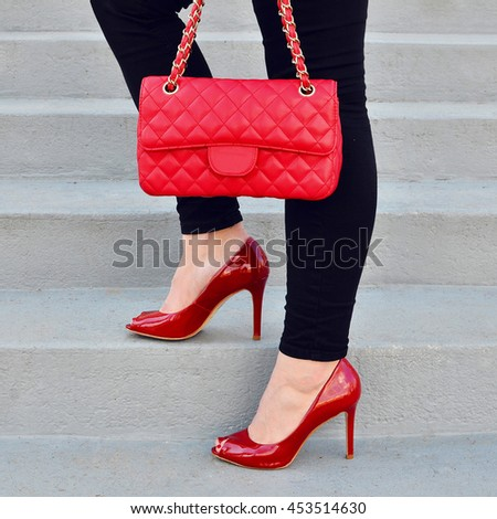 woman legs in red high heel shoes and red handbag on stairs