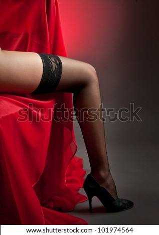 woman legs in stockings on red veil - stock photo