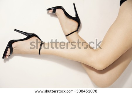 woman legs in stylish black heels, studio white