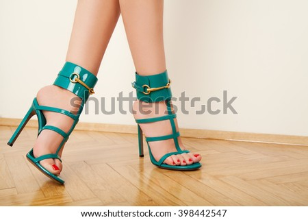 woman legs in stylish summer heels on wood floor