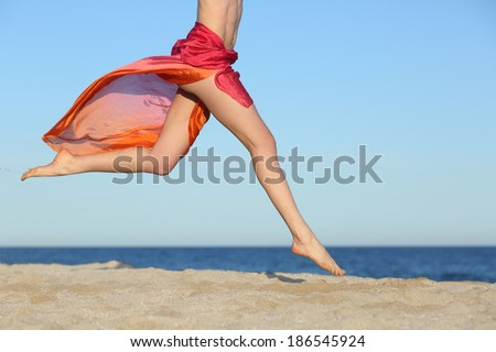 Woman legs jumping on the beach happy with the horizon and sea in the background             - stock photo