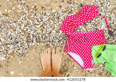 Woman legs near beach outfit. Summer beach accessories set, sunglasses and beach towel. Beach holiday concept - stock photo