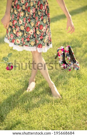 Woman legs on green grass throwing shoes and flower . Summer vacation concept. daylight, shadows - stock photo