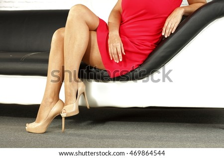 woman legs on sofa background in home room